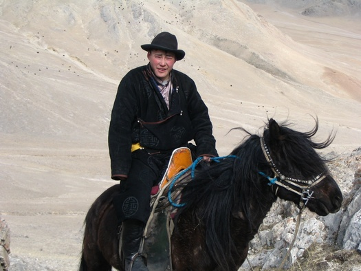 Young man in traditional Mongolian clothes on horse